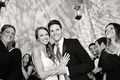 Black and white photo of bride and groom smile on dance floor at tent wedding