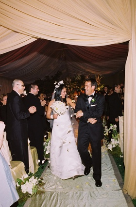 Bride and groom leaving ceremony space draped in buttercream fabric