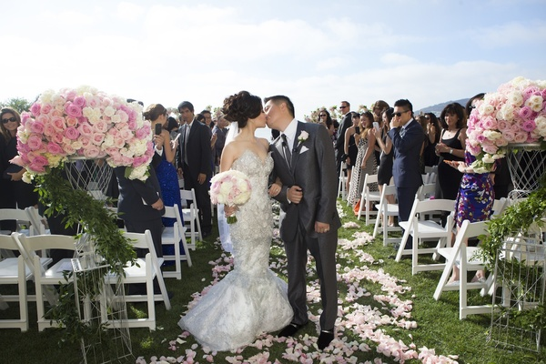 Bride and groom kiss at end of flower petal outdoor aisle