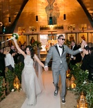 Bride in Monique Lhuillier wedding dress walking down aisle holding hands with Hunter Pence in grey