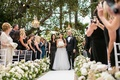 Bride in Monique Lhuillier wedding dress walks down aisle with mother of bride and father of bride