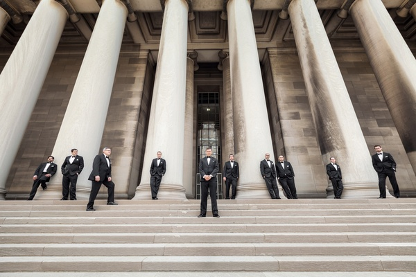 Men in tuxedos standing on stairs next to columns