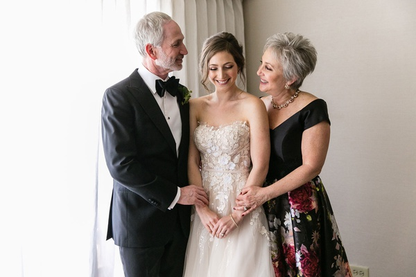 sweet moment with bride in mira zwillinger wedding dress mother in black and flower print gown