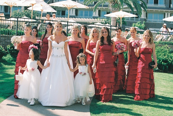 strapless red bridesmaid gowns with tiered skirts and white flower girl dresses