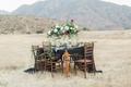 styled shoot tablescape dark motif black linen tall centerpieces wood chairs outside hills