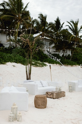 wedding reception lounge area white sofa cover wood table lanterns bistro lights green palms