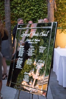 wedding seating chart written with white calligraphy on mirror