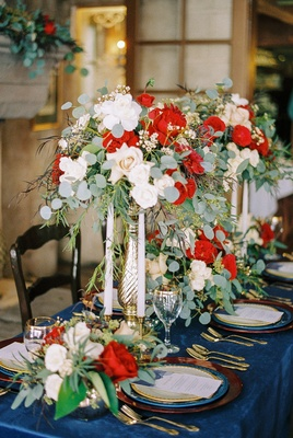 beauty beast movie styled wedding shoot silver vases red white flowers foliage candles blue linen