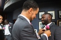 groomsman fixes groom's pink rose boutonniere