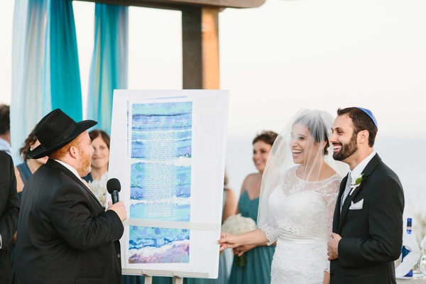 bride and groom smile at oceanfront ceremony with watercolor ketubah displayed at wedding