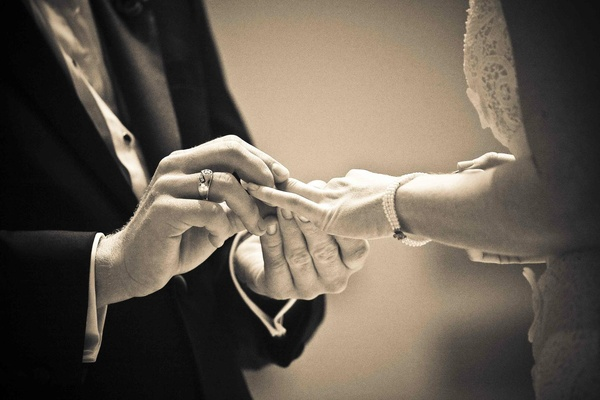 Black and white photo of groom putting on bride's wedding ring