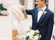 Bride in Carolina Herrera wedding dress ivory green bouquet with veil over face and groom smiling