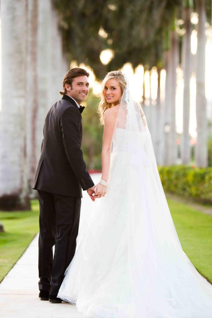 Bride and groom walk down palm tree-lined path