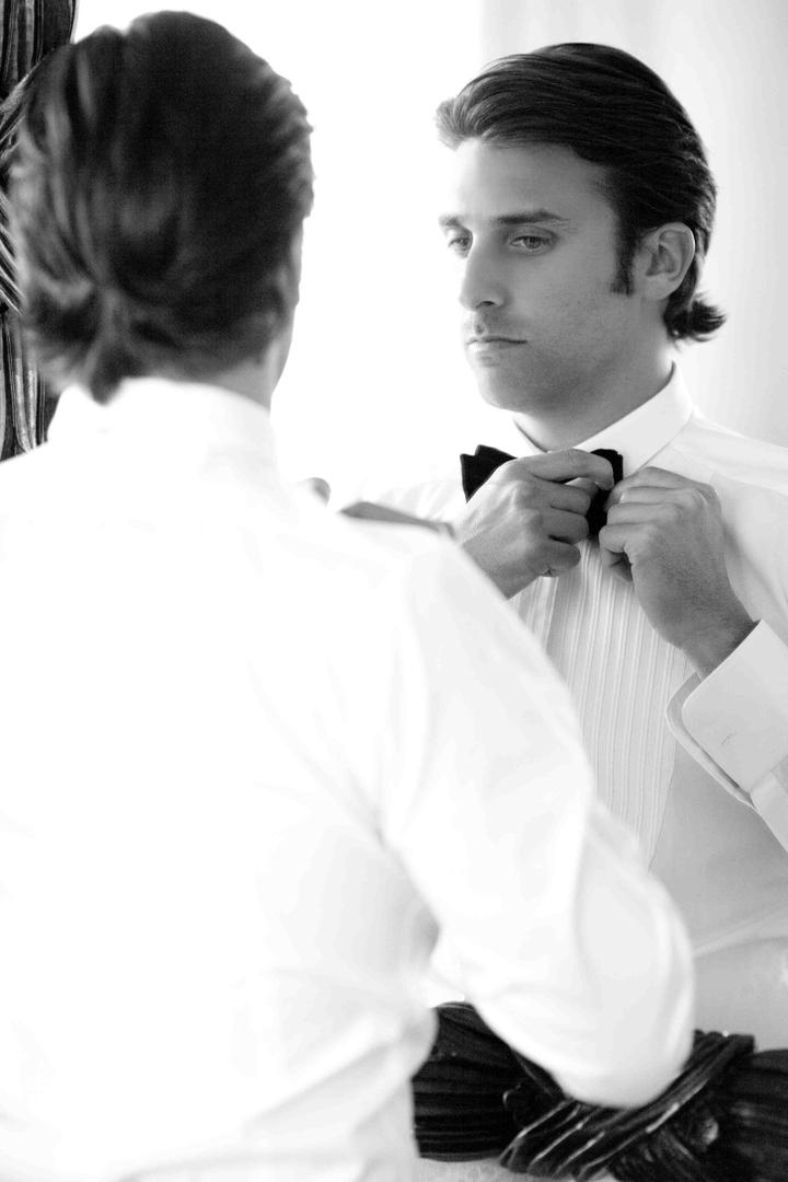 Black and white photo of groom in mirror tying bow tie