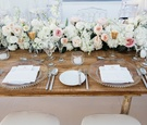 Beach wedding reception with a wood head table, runner of pink, peach, white garden roses, greenery