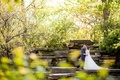 Bride in long sleeve lace wedding dress groom in navy blue suit on stones trees in Chicago
