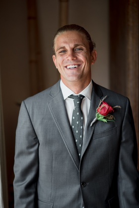 blond groom with man bun, charcoal grey suit with patterned tie, boutonniere made with dark red rose