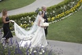 bride and father walk down path next to green lawn