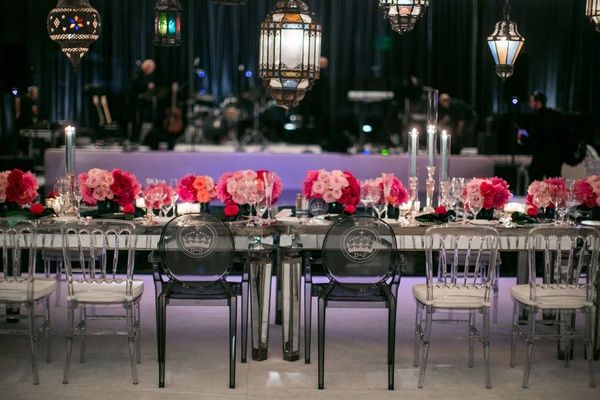 Ghost chairs with monogram at head table with pink low centerpieces