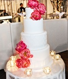 White wedding cake decorated with fresh pink peonies