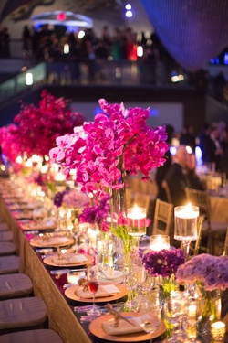 Wedding reception table with a mirror top, floating candles, and purple flowers