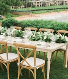 destination wedding reception hawaii wood table chairs green garland centerpiece beach view