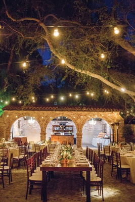 wedding reception long wood table short centerpiece bistro lights hanging from trees ranch courtyard