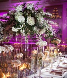 Hurricane vases with candles and white flowers at reception