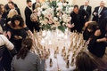 wedding guests looking for their names on escort card tags attached to miniature champagne bottles