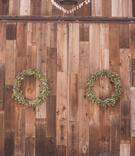 Green leaf wreath decor on rustic vintage barn doors at winery vineyard wedding reception location