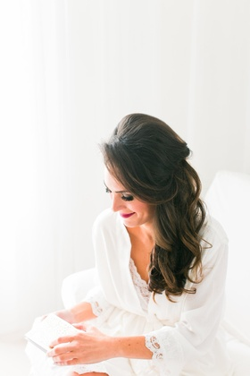 Bride with pretty brunette hair pulled back in white robe lace opening gift