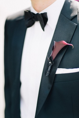 Burgundy calla lily boutonniere on groom tuxedo