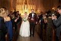 Bride in a line wedding dress strapless with groom in maroon suit tuxedo church wedding