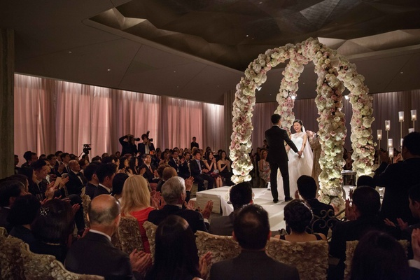 Bride and groom holding hands at wedding ceremony in ballroom under two flower arches candlelit