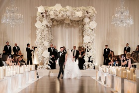 Bride and groom doing seven circles tradition jewish wedding chuppah white flowers orchid rose