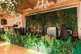 wedding reception band in front of ivy with greenery hedge and iron gate in front