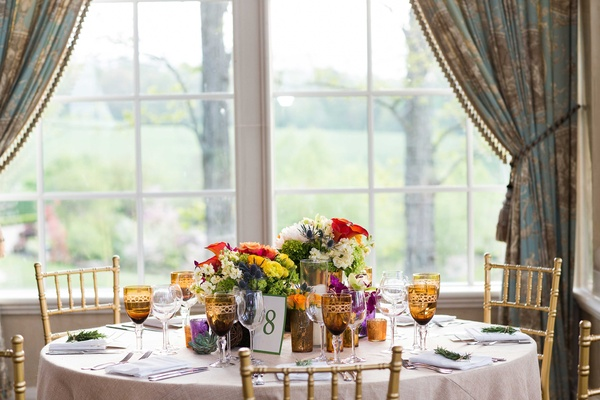bright colored flowers and rustic reception décor in front of glass windows with curtains