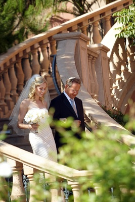 Father of bride walks bride down flight of stairs to ceremony
