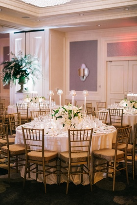 Wedding reception round table with gold chairs low flower centerpiece and tall taper candles shades