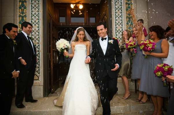Bride in a Monique Lhuillier gown and groom in a tuxedo leaving ceremony