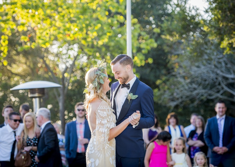 bohemian bride and groom in unique detailed wedding dress in off white and navy blue tuxedo dance