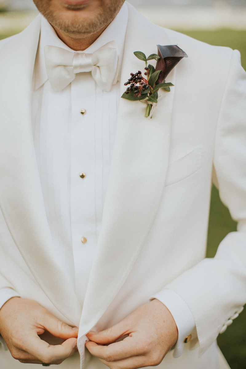 groom in white tuxedo jacket bow tie gold buttons dark burgundy calla lily boutonniere greenery
