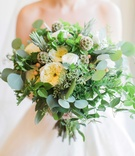 Bride holding bouquet with eucalyptus leaves, white garden roses, scabiosa pods, rosemary, thyme