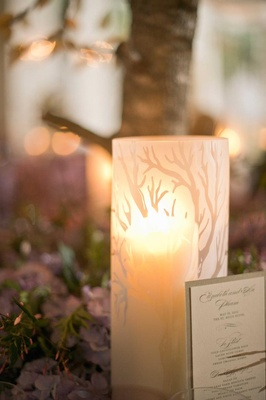 Tree motif on glass candle vessel on reception table