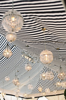 Gold-rimmed globes suspended from striped tent