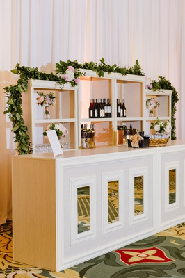 wedding reception ballroom white mirror bar with shelves garland pink blush flowers wine