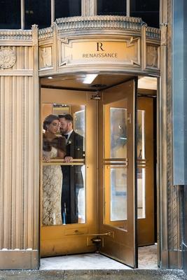 Bride with fur bolero and groom in tuxedo at Renaissance Hotel revolving gold door