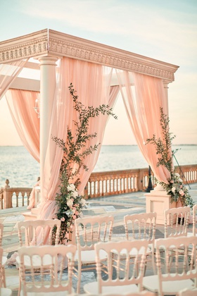ornate chuppah with blush drapery and greenery crawling up the sides