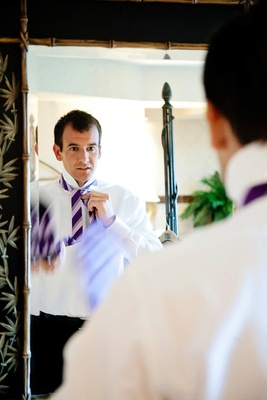 Man tying purple striped tie in mirror