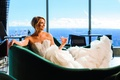 bride in strapless lazaro corset dress with ruffled train holding cocktail in emerald green chaise